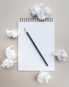 Conceito de escrita - amassado maços de papel com uma folha de papel branco e lápis.