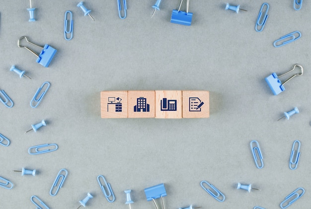 Conceito de escritório de negócios com blocos de madeira com ícones, clipes de papel, vista superior de clipes de pasta.