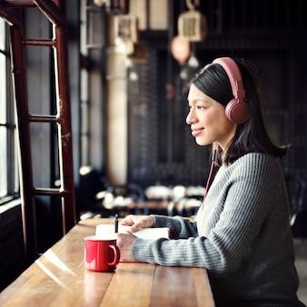 Conceito de escuta da música da cafetaria do passatempo da mulher