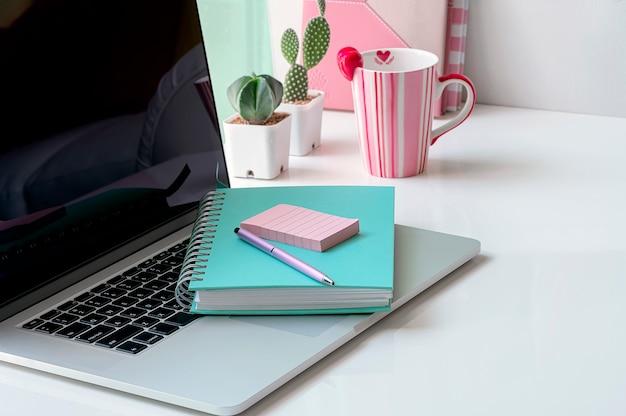 Conceito de espaço de trabalho com caderno verde e caneta no laptop.