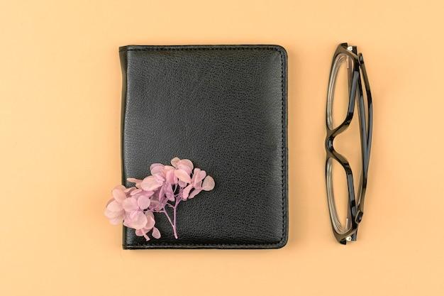 Conceito de espaço de trabalho mínimo com caderno de couro preto, flor rosa seca e óculos, foto de composição de vista superior