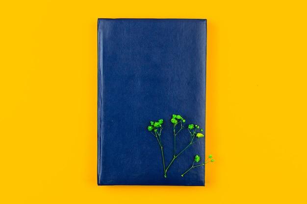 Conceito de espaço de trabalho mínimo e comercial com caderno de couro azul, composição de floal, foto plana e vista superior