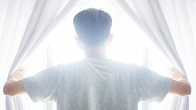 Conceito de esperança. homem cortina aberta ver o nascer do sol