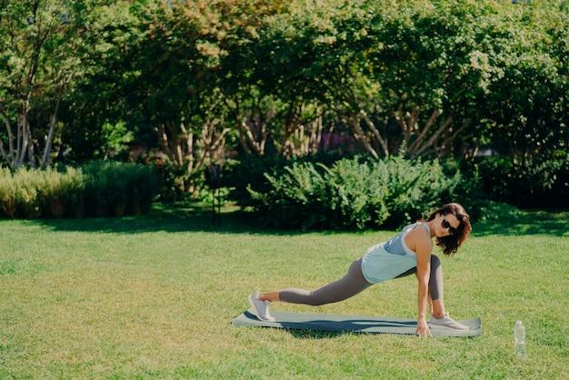Conceito de esporte ao ar livre. mulher jovem enérgica de ajuste saudável faz exercícios de fitness na esteira de aptidão vestida com roupa ativa bebe água doce usa óculos de sol poses na grama verde. treino matinal.