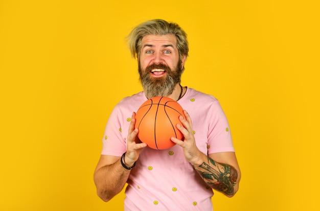 Conceito de esporte. aproveite o jogo. jogue com a bola de basquete. homem feliz jogando. hobby e lazer. estilo de vida saudável. cara ativo. jogadores de basquete em fundo amarelo. jogador de basquete moderno.