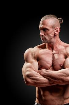 Conceito de esporte. atleta de fitness com músculos perfeitos posa na câmera sobre espaço preto.