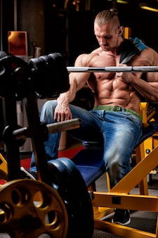 Conceito de esporte. atleta de fitness com músculos perfeitos posa na câmera sobre parede preta
