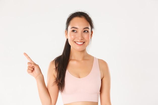 Conceito de esporte, bem-estar e estilo de vida ativo. close-up da garota asiática atraente fitness sorridente, atleta feminina, escolhendo novos equipamentos na loja, apontando e olhando o canto superior esquerdo satisfeito.