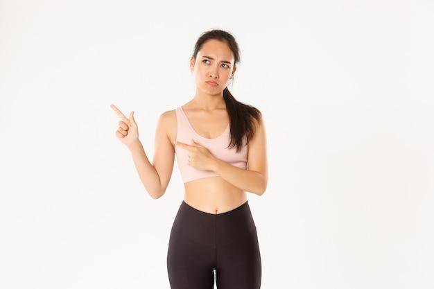 Conceito de esporte, bem-estar e estilo de vida ativo. menina asiática triste reclamando de roupas esportivas, carrancuda e carrancuda chateada ao apontar o canto superior esquerdo, fim da oferta de venda, parede branca em pé