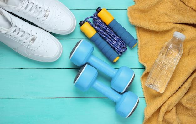 Conceito de esporte de estilo liso leigo. halteres, tênis, corda de pular, garrafa de água com toalha. equipamento desportivo em fundo azul de madeira.