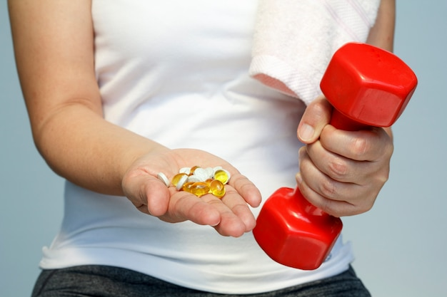 Conceito de esporte e dieta - mão de mulher com vitaminas e medicamentos