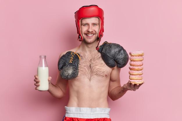 Conceito de esporte e nutrição de pessoas. boxeador magro positivo posa com o torso nu sorrindo e tem a tentação de comer donuts e beber leite