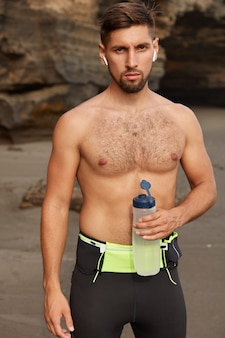 Conceito de esporte e recreação. desportista motivado tem treino cardiovascular na praia