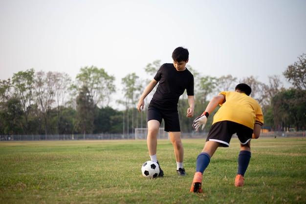 Conceito de esporte e recreação dois jogadores de futebol do sexo masculino participando de sessões de treinos regulares e memorizando padrões de ataque e defesa.