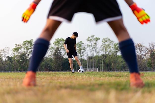 Conceito de esporte e recreação: um jogador amador praticando a posição de goleiro e ensaiando para pegar a bola na cobrança de falta.