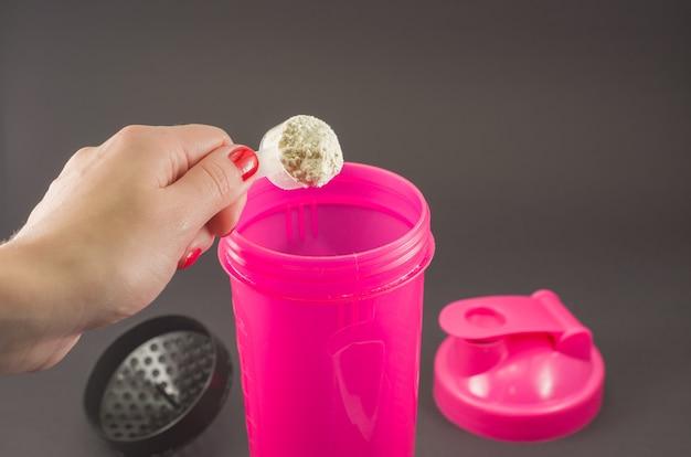 Conceito de esporte, fitness, estilo de vida saudável e pessoas - close-up de mulheres com jarra e garrafa preparando o shake de proteína