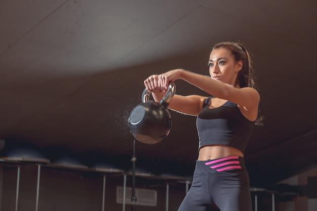 Conceito de esporte, fitness, levantamento de peso e treinamento. grupo de pessoas com kettlebells e rastreadores de freqüência cardíaca, exercitando-se no ginásio