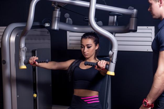 Conceito de esporte, fitness, trabalho em equipe e pessoas. jovem mulher flexionando os músculos na máquina de ginástica e personal trainer com prancheta