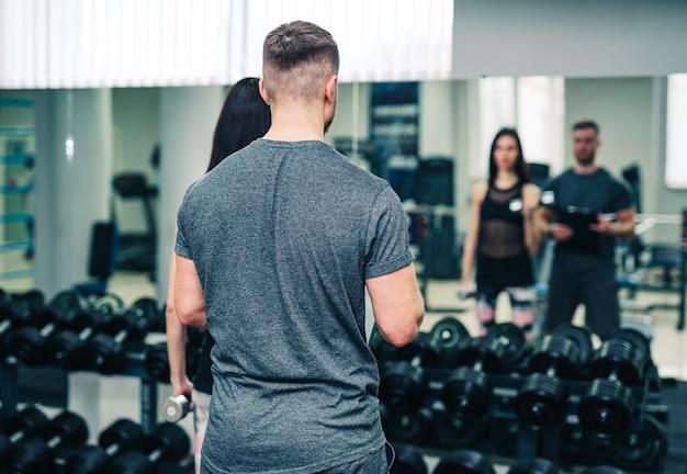 Conceito de esporte, fitness, trabalho em equipe, levantamento de peso e pessoas - jovem e personal trainer com halteres flexionando os músculos na academia