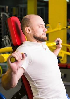 Conceito de esporte, fitness, treinamento e pessoas - homem musculoso, fazendo exercícios pesados bombeando os músculos no ginásio.