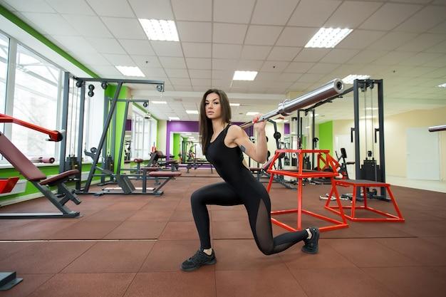 Conceito de esporte, musculação, estilo de vida e pessoas - mulher com barra flexionando os músculos e fazendo estocada de ombro na academia