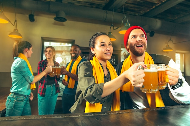 Conceito de esporte, pessoas, lazer, amizade e entretenimento - fãs de futebol felizes ou amigos do sexo masculino bebendo cerveja e comemorando a vitória em um bar ou pub