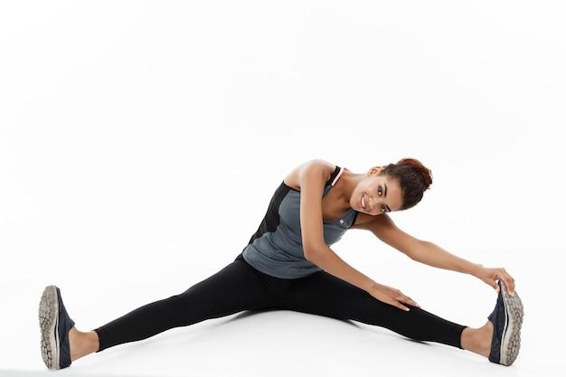 Conceito de esporte, treinamento, estilo de vida e fitness - retrato de uma mulher afro-americana feliz, esticando a perna enquanto está sentado. isolado no branco.