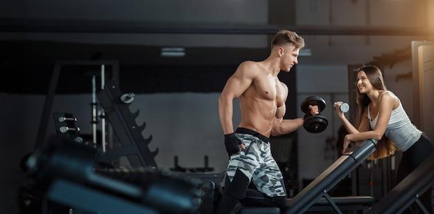 Conceito de esporte, treinamento, fitness, estilo de vida e as pessoas - jovem com personal trainer, flexionando os músculos traseiros e abdominais no banco no ginásio