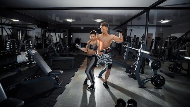 Conceito de esporte, treinamento, fitness, estilo de vida e pessoas - jovem com personal trainer, flexionando os músculos abdominais e costas no banco no ginásio. foto de alta qualidade