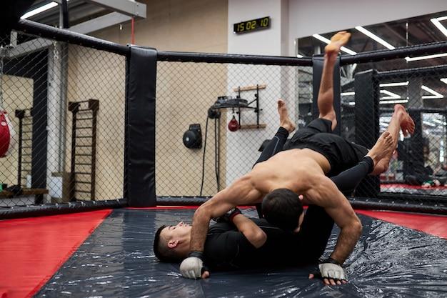 Conceito de esportes de luta sem regras. dois lutadores confiantes no ginásio, treinando juntos. lutas sem regras de boxe mma. visão lateral de batalhas esportivas