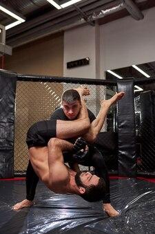 Conceito de esportes de luta sem regras. dois lutadores de atleta no ginásio, treinando juntos. lutas sem regras de boxe mma. visão lateral de batalhas esportivas