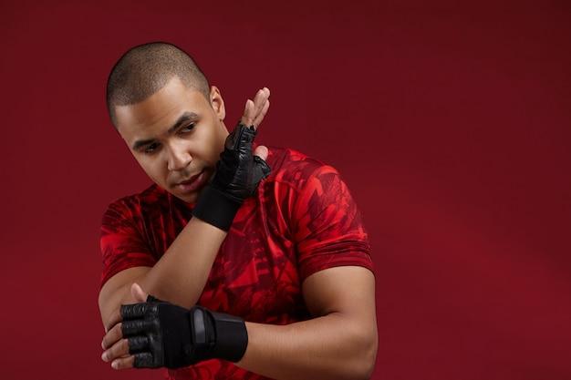 Conceito de esportes e artes marciais. foto horizontal de um jovem boxeador africano forte vestindo uma camiseta vermelha e luvas sem dedos de treinamento de boxe tailandês, dominando suas habilidades na academia, com foco na expressão facial