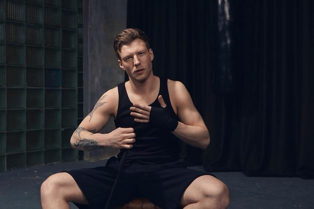 Conceito de esportes e artes marciais. retrato de jovem bonito em forma de homem com tatuagens nos braços, sentado dentro de casa e amarrando bandagens de boxe no pulso, preparando-se para o treinamento, com olhar confiante