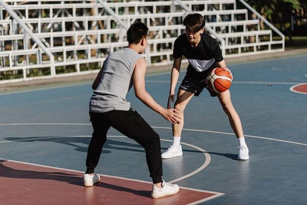 Conceito de esportes e recreação dois jogadores masculinos de basquete, desfrutando de jogar basquete juntos no campo de esportes.