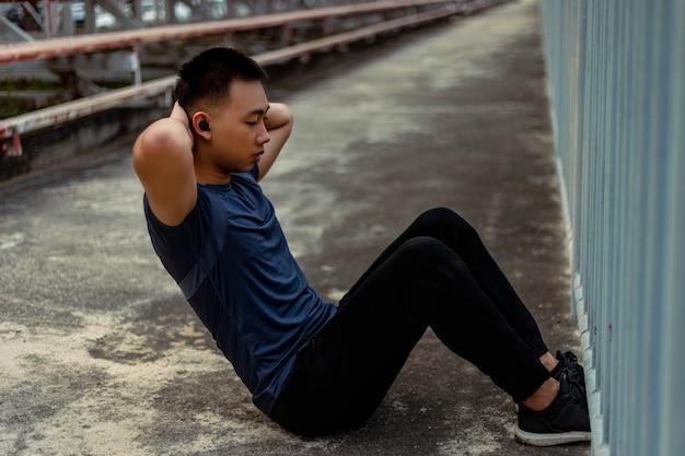 Conceito de esportes e recreação: um adolescente do sexo masculino fazendo movimentos de aquecimento, aumentando a temperatura corporal e aumentando o fluxo sanguíneo para os músculos.
