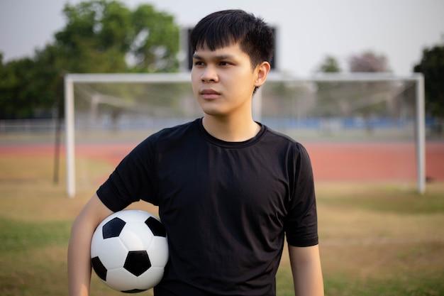 Conceito de esportes e recreação um adolescente do sexo masculino, usando a mão direita segurando uma bola de um lado no meio do campo de futebol.
