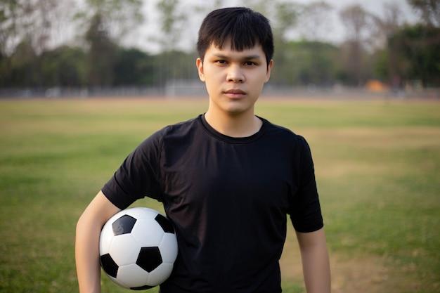 Conceito de esportes e recreação um adolescente do sexo masculino, usando a mão direita segurando uma bola de um lado no meio do campo de futebol. Foto Premium