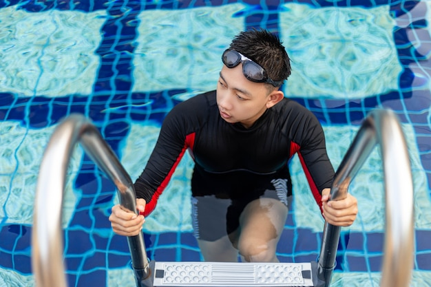 Conceito de esportes e recreação, um adolescente do sexo masculino usando óculos de proteção e maiô vermelho e preto saindo da piscina depois de nadar.