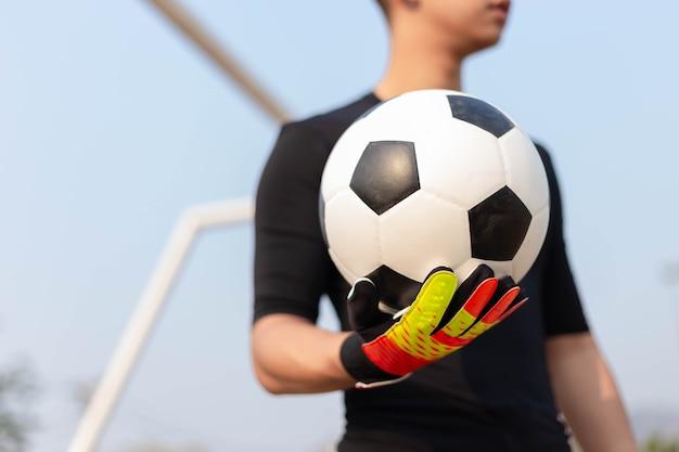 Conceito de esportes e recreação, um goleiro adolescente do sexo masculino, vestindo roupa preta e um par de luvas coloridas, segurando uma bola de futebol.