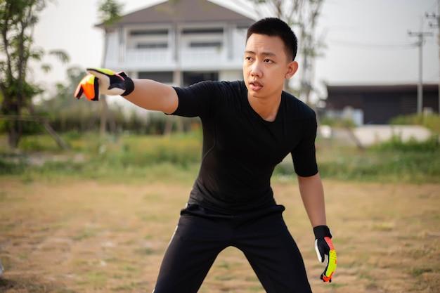 Conceito de esportes e recreação um goleiro em frente ao gol, jogando uma bola e distribuindo para um jogador depois de proteger o gol.