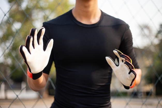 Conceito de esportes e recreação um jogador amador do sexo masculino praticando como posição de goleiro, ensaiando para pegar a bola.