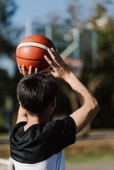 Conceito de esportes e recreação, um jovem adolescente do sexo masculino praticando arremesso de uma bola de basquete separadamente na quadra depois da escola.