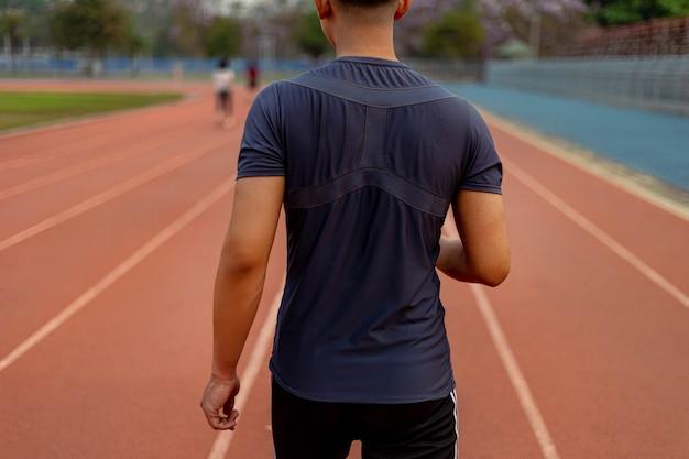 Conceito de esportes e recreação, um jovem adulto do sexo masculino correndo em baixa velocidade no estádio esportivo como sua rotina saudável à noite.