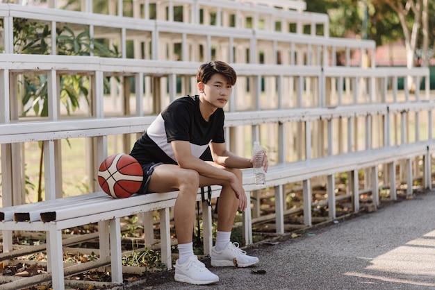 Conceito de esportes e recreação, um jovem jogador de basquete masculino sentado em uma arquibancada na fronteira da quadra de esportes.