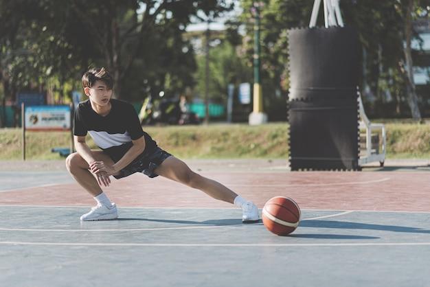 Conceito de esportes e recreação um menino asiático em roupas pretas, esticando as pernas antes de jogar basquete em uma quadra de basquete.