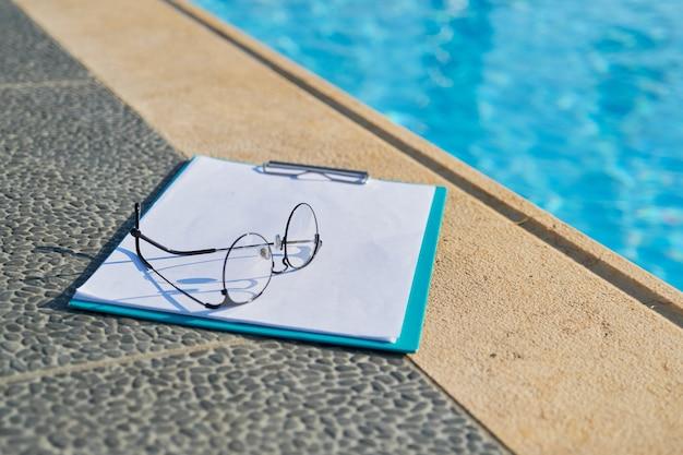 Conceito de esportes, estilo de vida ativo e saudável, hotel de negócios. ninguém, óculos, papel em branco, prancheta perto da piscina do resort