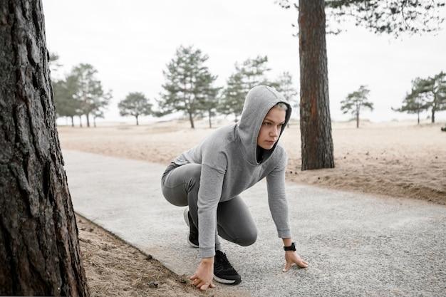 Conceito de esportes, fitness, bem-estar, saúde, energia e competição. imagem ao ar livre de uma jovem atleta concentrada com capuz e tênis, sentada em uma posição estável na trilha pavimentada, pronta para correr