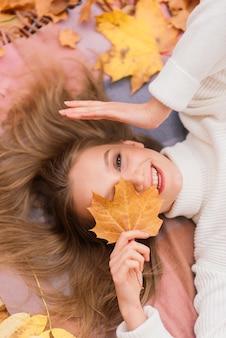 Conceito de estação e povo - bela jovem com folhas de bordo de outono deitada no chão