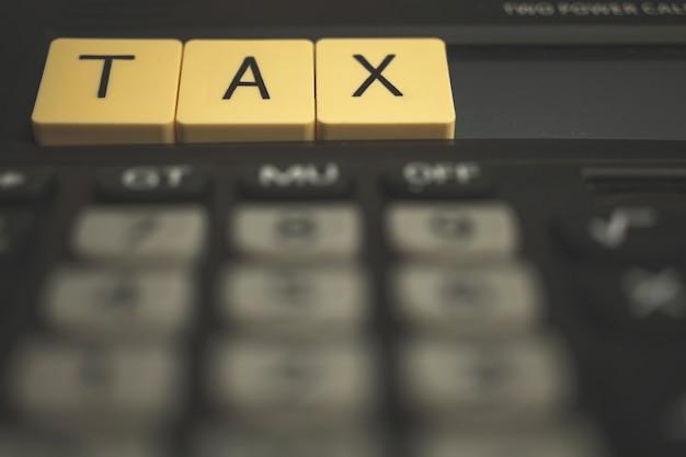 Conceito de estação fiscal com blocos de madeira e calculadora, foto de fundo 1040 do negócio