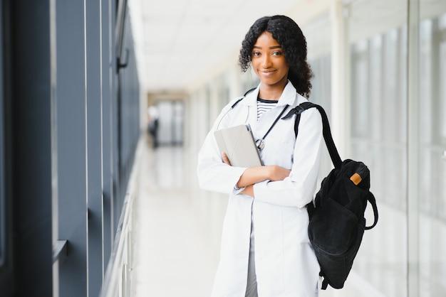 Conceito de estágio médico. retrato de uma jovem estudante negra de médico no casaco branco.